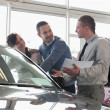 Salesman and a couple looking at a car — Stock Photo