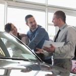 säljare och ett par tittar på en bil — Stockfoto