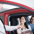 Couple sitting in a car receiving key from a car dealer - Stock Photo