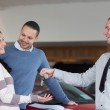 Couple embracing while receiving keys from a salesman — Stock Photo #14077372