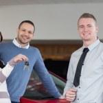 Salesman giving keys to an embracing couple — Stock Photo #14077373