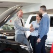 Man shaking hand of a car dealer in front of a car — Stock Photo