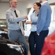 Salesman giving car key to a couple - Stock Photo