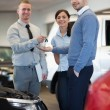 Smiling salesman handing keys to a happy couple — Stock Photo