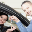 Man giving car keys to a woman - Stock Photo