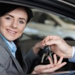 Smiling woman in a car receiving car keys — Stock Photo