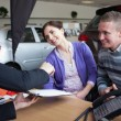 Stock Photo: Couple chatting with a car salesman