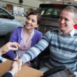 Happy couple shaking the hand of a salesman — Stock Photo