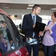 Salesman talking to a smiling woman next to a car — Stock Photo