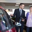 Salesman showing a car to a woman — Stock Photo