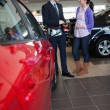 Foto Stock: Womsmiles as she talks with salesman