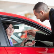 Smiling woman receiving car keys - Stock Photo