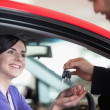 Woman smiling while receiving car keys - Stock Photo