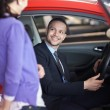Man sitting in a car while talking to a woman — Stock Photo