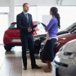 Salesman and a woman talking next to a car - Stock Photo