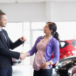 Salesman shaking the hand of a woman and giving her car keys — Stock Photo