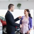 Woman shaking the hand of a salesman while receiving car keys — Stock Photo