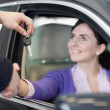 Woman in a car while shaking a hand and receiving car keys - Stock Photo