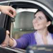Stock Photo: Womin car while shaking hand and receiving car keys