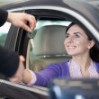Woman smiling in a car while shaking hand - Stock Photo