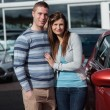 Royalty-Free Stock Photo: Couple holding tight while standing next to a car