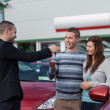 Salesman giving car keys to a couple — Stockfoto