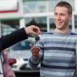 Couple receiving car keys by a dealer - Stock Photo