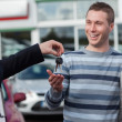 Foto Stock: Couple receiving car keys by dealer
