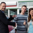 Dealer shaking hand of a man while giving him car keys — Stock fotografie