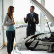 Businessmpresenting car to woman — Stock Photo #14078137