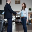Dealer shaking hand of a woman — Stock Photo