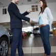 Stock Photo: Salesmgiving car keys while shaking hand of client