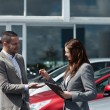 Businesswoman giving car keys to a client — Stok fotoğraf
