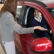 Businesswoman presenting the car to a client — Stock Photo #14078285
