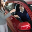 Businesswoman giving car keys to a customer — Stock Photo #14078287