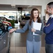Businesswoman presenting a car to a client — Stock Photo