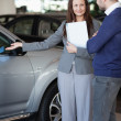 Woman showing a car to a client — Stock Photo