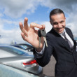 Happy dealer holding car keys — Stockfoto #14078475
