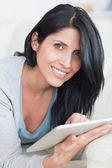 Close up of a smiling woman playing with a tablet — Stock Photo