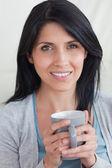 一个女人同时拿一杯微笑的特写 — 图库照片