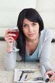 Woman lying on the floor while holding a glass of wine and a mag — Stock Photo