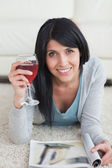 Woman smiling while holding a glass of wine and a magazine on th — Stock Photo