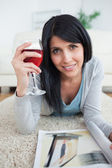 Woman smiling while holding a magazine and a glass of red wine — Stock Photo