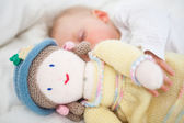 Baby sleeping while holding a plush doll — Stock Photo