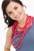 Blue eyed brunette posing with a red bead necklace — Photo