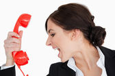 Woman in suit shouting against a red dial telephone — Stock Photo