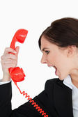Woman in suit screaming on a red dial telephone — Stock Photo