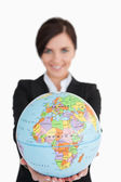 Brunette businesswoman holding an earth globe — Stock Photo