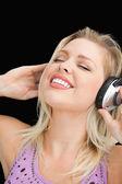 Joyful blonde woman listening to music with headphones — Stock Photo