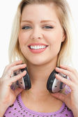 Smiling blonde woman standing while holding headphones — Stock Photo